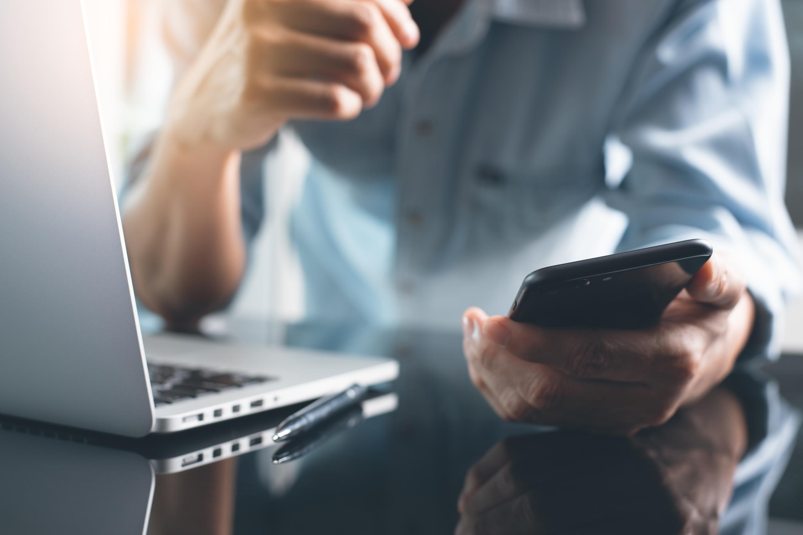 Bild: Mann mit Handy und Laptop